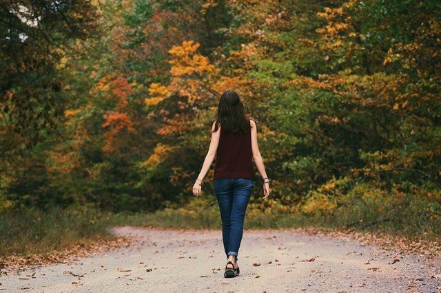 a woman walking on a road in the fall