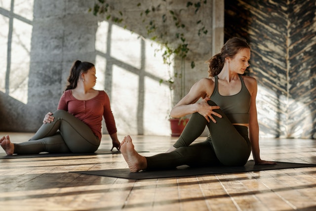 two women practicing Yoga in a sunny studio